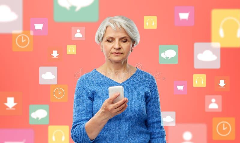 Hög kvinna med smartphonen över mobila appsymboler royaltyfri foto