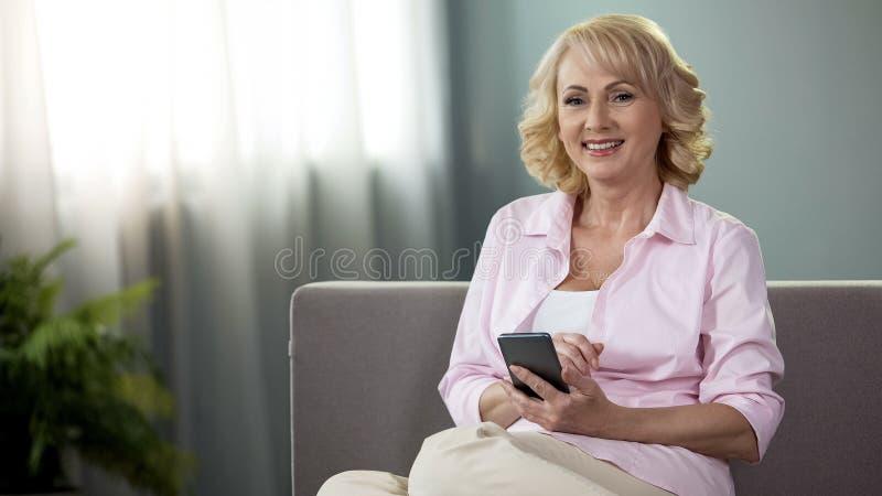 Hög kvinna med smartphonen som in camera ler och direktanslutet att packa ihop, finansiell app royaltyfri bild