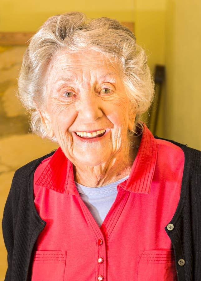 Hög kvinna, nittio plus år och att le, tillfällig kläder, medel royaltyfri bild
