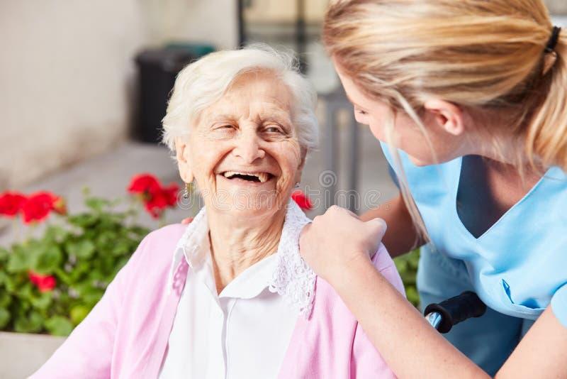 Hög kvinna och att bry sig den geriatriska sjuksköterskan arkivfoto