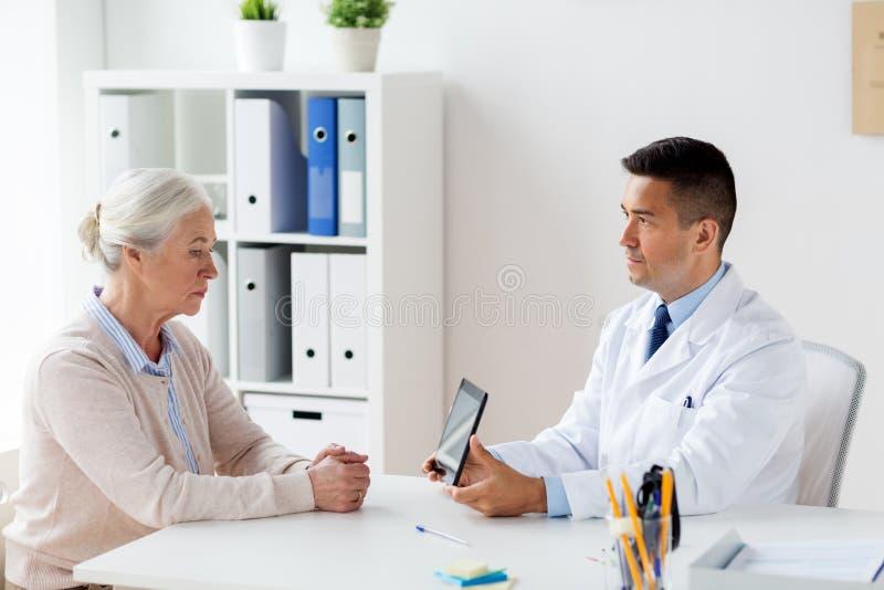 Hög kvinna och doktor med minnestavlaPC på sjukhuset royaltyfria foton