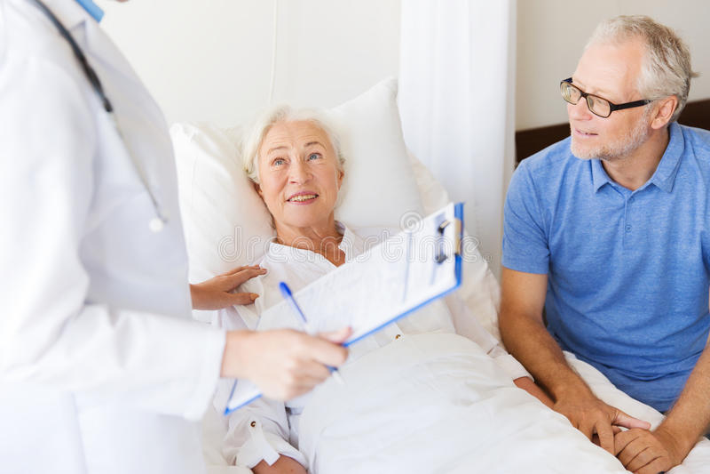 Hög kvinna och doktor med skrivplattan på sjukhuset arkivfoto