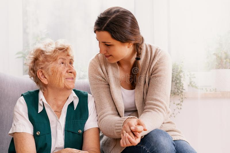 Hög kvinna och hjälpsam volontär på vårdhemmet royaltyfri bild