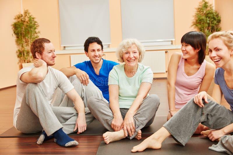 Hög kvinna och lycklig grupp människor på konditionmitten royaltyfri fotografi
