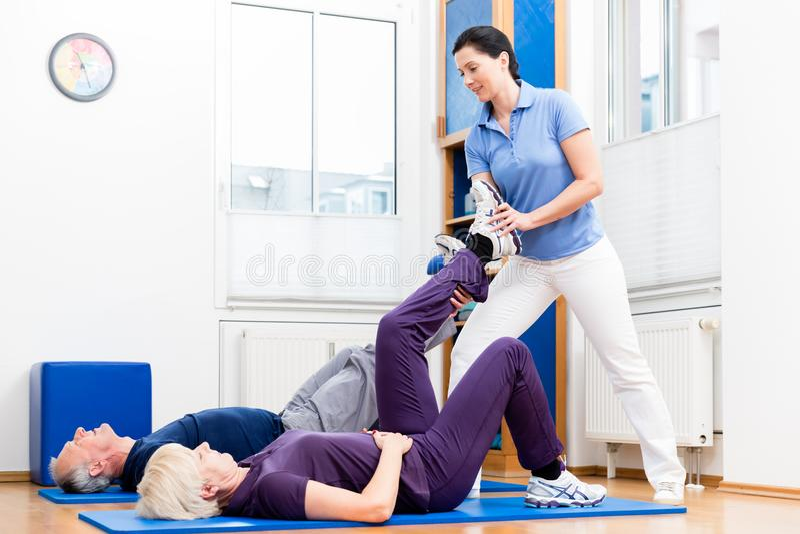 Hög kvinna och man som gör hjälpta golvövningar med physiot arkivbilder