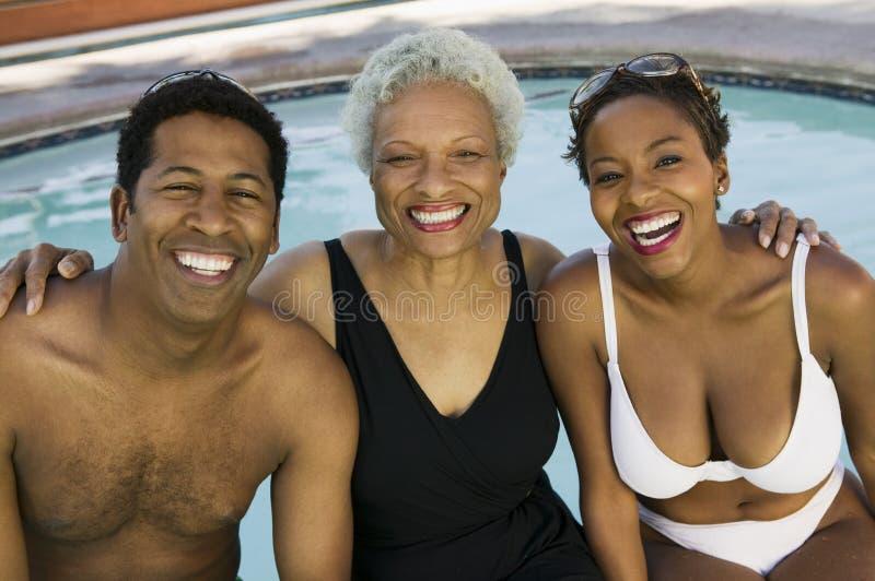 Hög kvinna och par på simbassängståenden. royaltyfria bilder