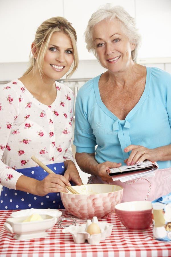 Hög kvinna- och vuxen människadotterbakning i kök arkivfoton