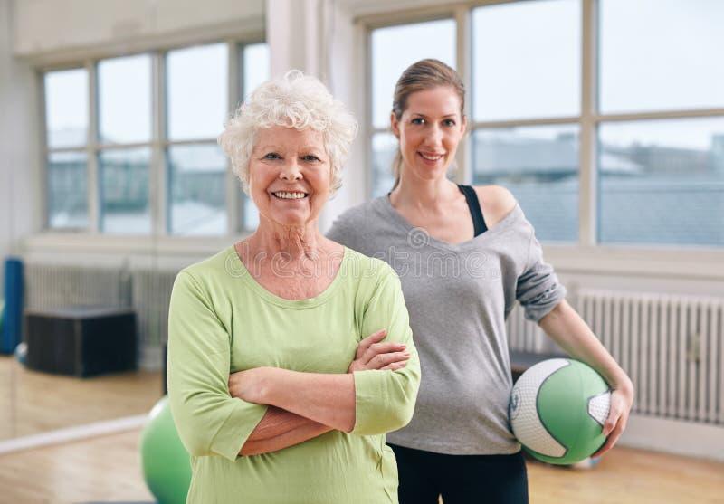 Hög kvinna på den vård- klubban med idrottshallinstruktören royaltyfria foton