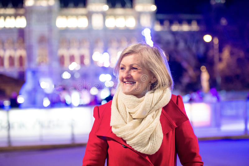 Hög kvinna på en gå i nattstad Vinter arkivbild