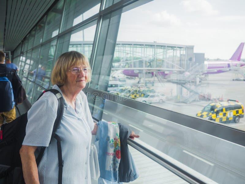 Hög kvinna på flygplatsen royaltyfria bilder