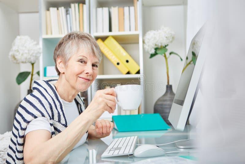 Hög kvinna på hennes skrivbord arkivbilder
