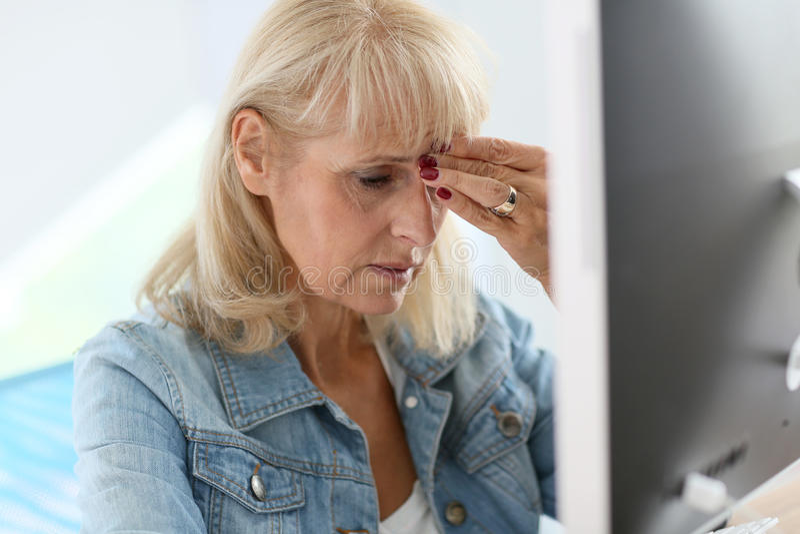Hög kvinna på kontoret som lider en huvudvärk arkivfoto