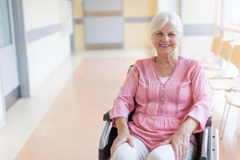 Hög kvinna på rullstolen i sjukhus arkivbild
