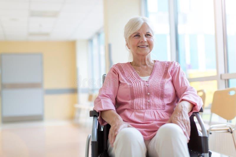 Hög kvinna på rullstolen i sjukhus royaltyfria foton