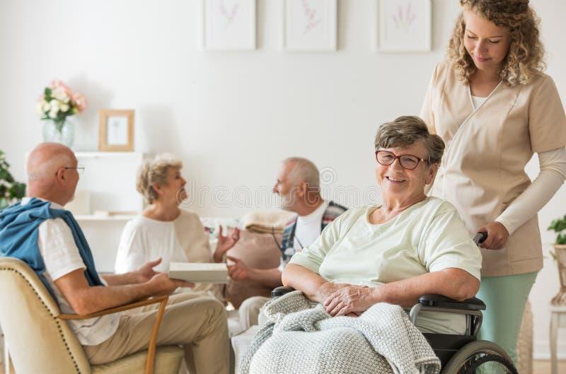 Hög kvinna på rullstolen med den yrkesmässiga anhörigvårdaren som stöttar henne arkivbilder