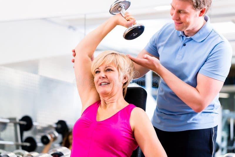 Hög kvinna på sportövningen i idrottshall med instruktören royaltyfria foton
