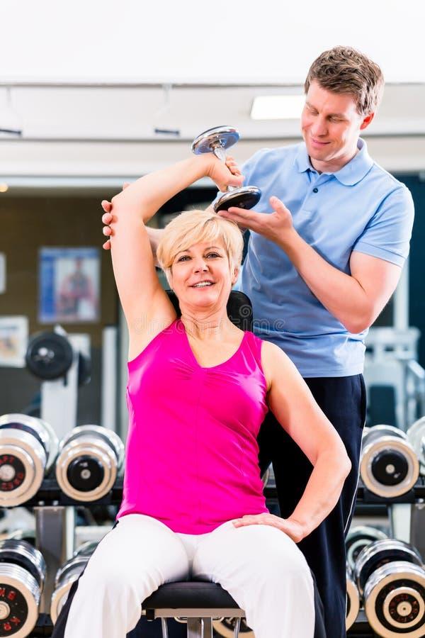Hög kvinna på sportövningen i idrottshall med instruktören fotografering för bildbyråer