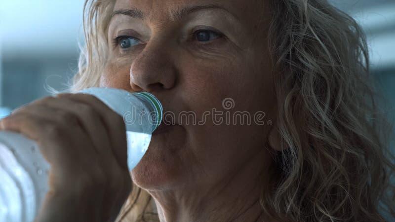 Hög kvinna på trampkvarnen i idrottshallen som lyssnar till musik med hörlurar och dricksvatten från en flaska, slut upp fotografering för bildbyråer