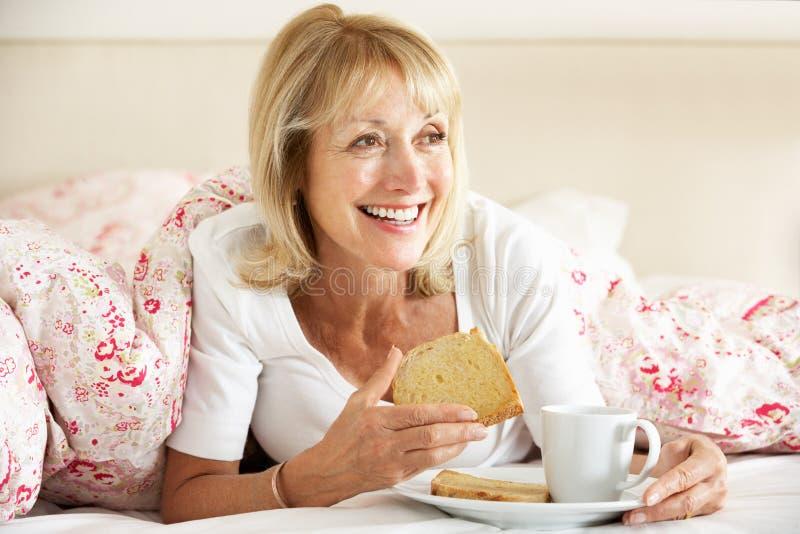 Hög kvinna Snuggled under duveten som äter frukosten royaltyfria foton