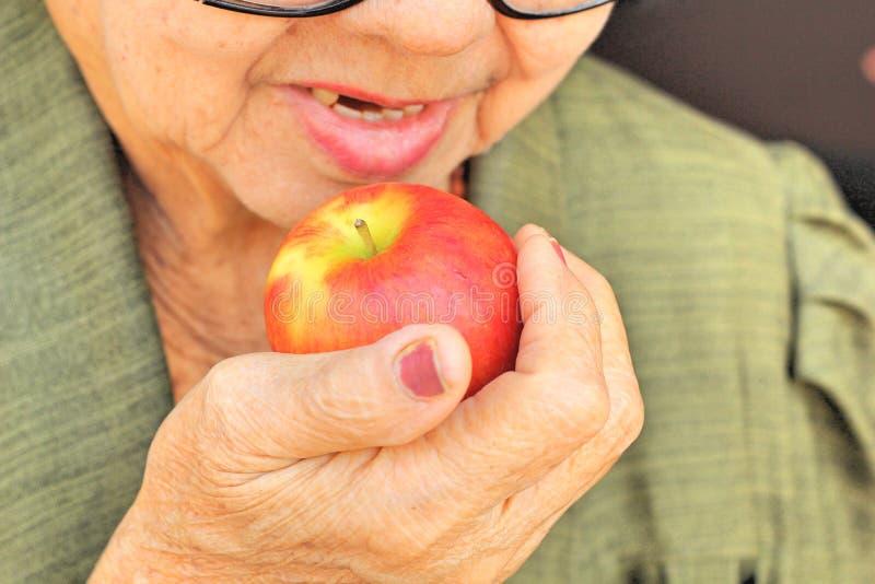Hög kvinna som äter ett rött äpple royaltyfri bild