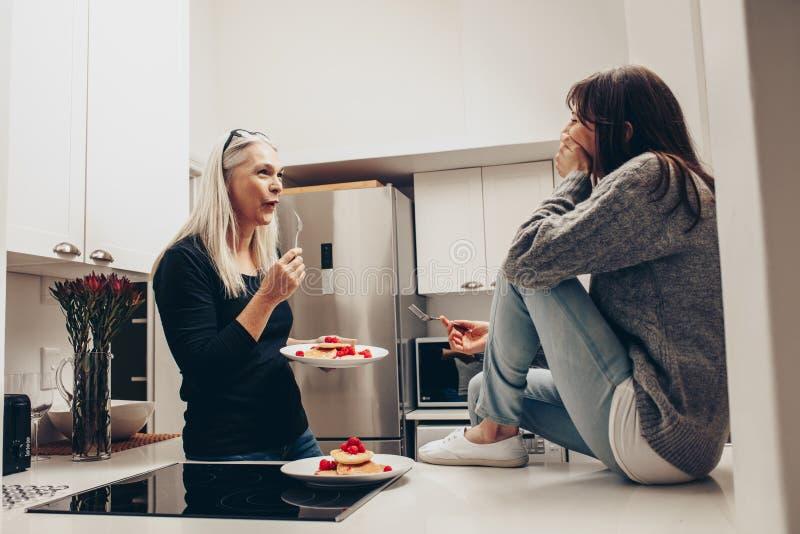Hög kvinna som äter kakor från ett plattaanseende i kök som talar till en kvinna Två kvinnor som talar, medan äta mellanmål i kök royaltyfria foton