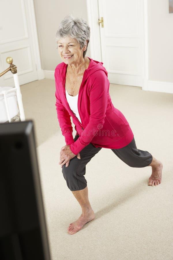 Hög kvinna som övar hållande ögonen på kondition DVD för stund på television royaltyfri fotografi