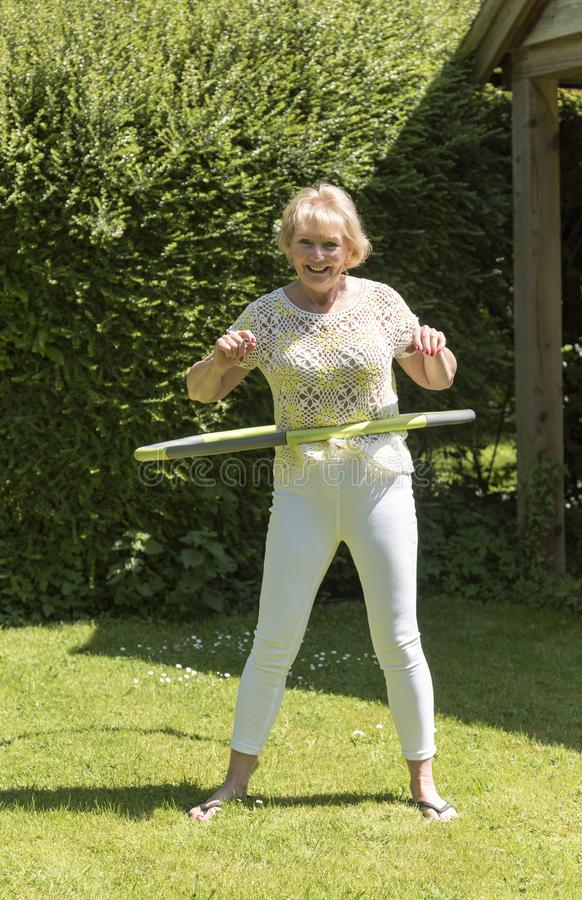 Hög kvinna som övar i en trädgård royaltyfri fotografi