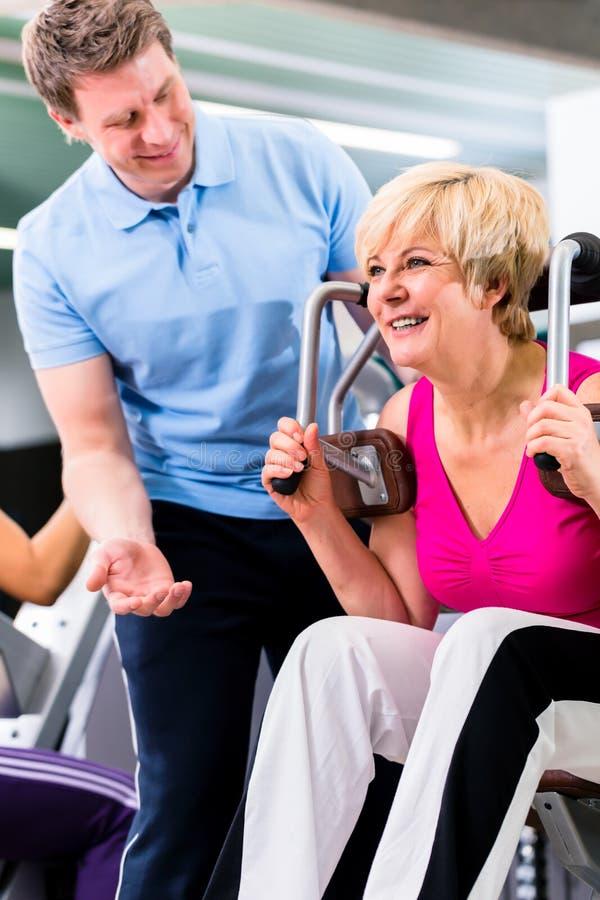 Hög kvinna som övar med den personliga instruktören i idrottshall royaltyfria foton