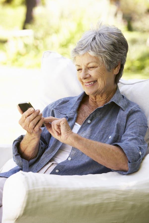 Hög kvinna som överför sammanträde för textmeddelande på soffan arkivfoton