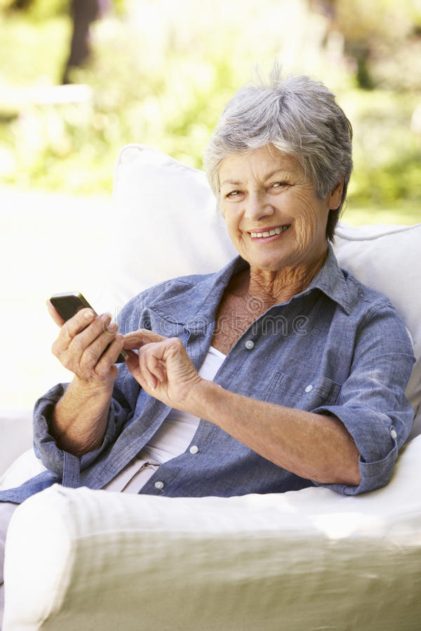Hög kvinna som överför sammanträde för textmeddelande på soffan royaltyfri fotografi