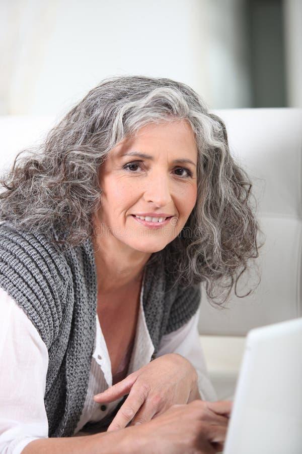Hög kvinna som använder bärbara datorn arkivfoton