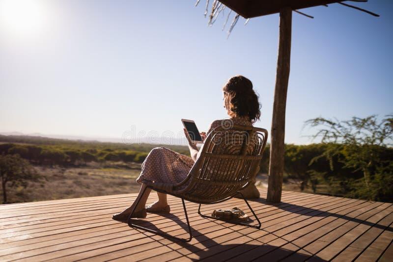 Hög kvinna som använder den digitala minnestavlan, medan sitta royaltyfri fotografi