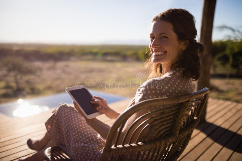 Hög kvinna som använder den digitala minnestavlan, medan sitta arkivfoto
