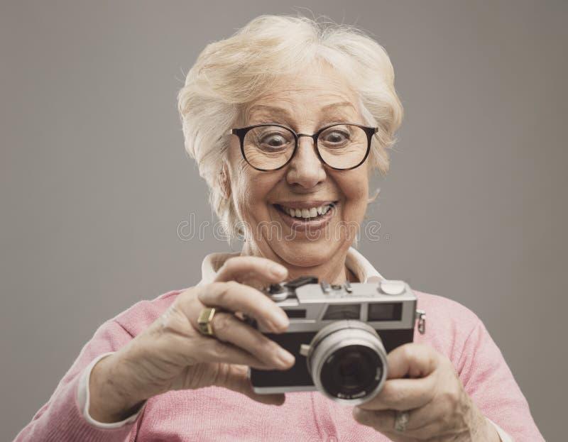 Hög kvinna som använder en digital kamera arkivfoto