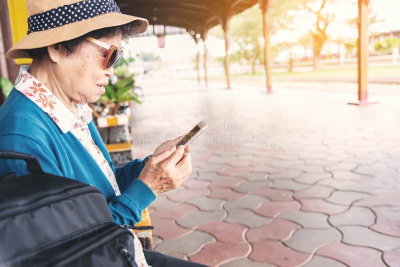 Hög kvinna som använder en mobiltelefon i drevstation royaltyfri foto