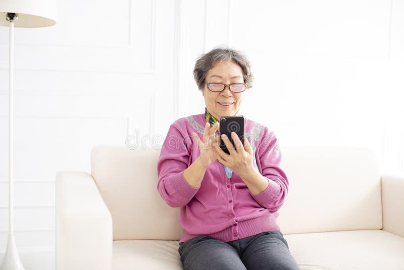 Hög kvinna som använder mobiltelefonen, medan sitta på soffan royaltyfri foto