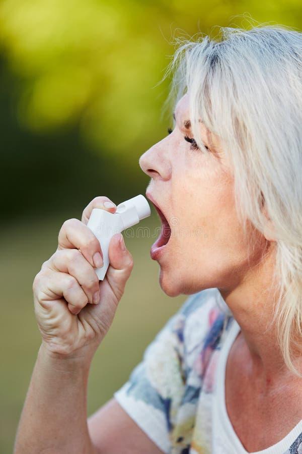 Hög kvinna som använder sprej mot astma royaltyfri foto