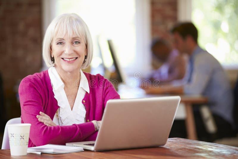 Hög kvinna som arbetar på bärbara datorn i modernt kontor royaltyfria bilder