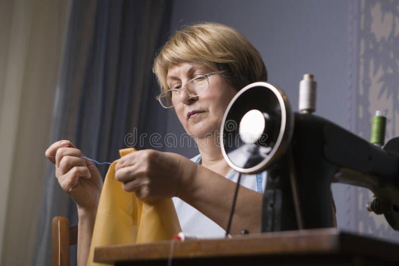 Hög kvinna som arbetar på symaskinen arkivfoto
