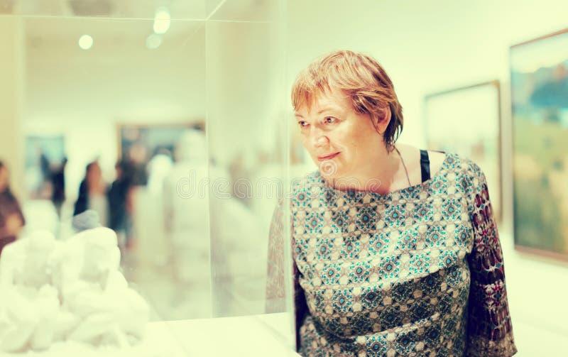 Hög kvinna som besöker museet och tillfredsställer royaltyfria foton