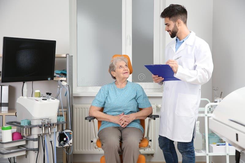 Hög kvinna som besöker otolaryngologisten i klinik arkivbilder