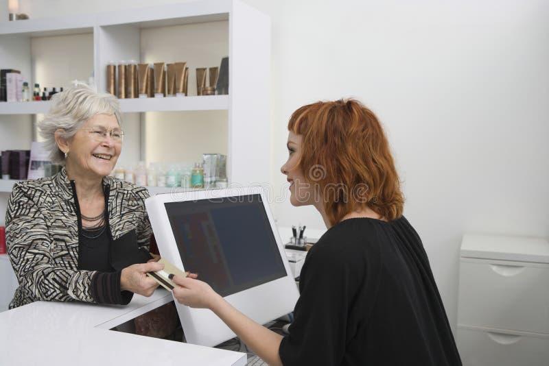 Hög kvinna som betalar för hennes frisyr på mottagandeskrivbordet royaltyfria foton
