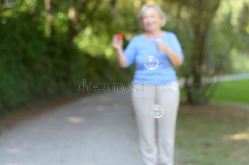 Hög kvinna som blåser regnbågsskimrande såpbubblor arkivbild