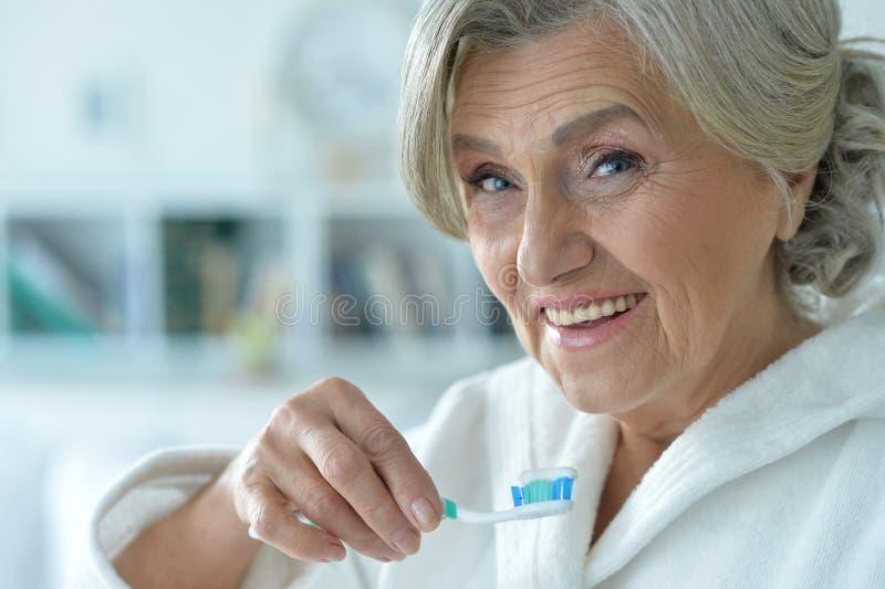 Hög kvinna som borstar hennes tänder arkivfoton