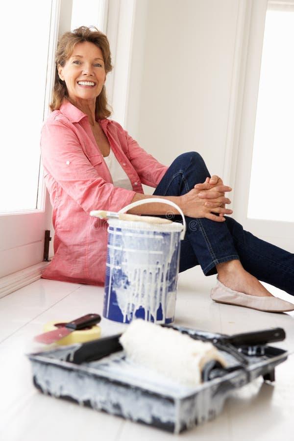 Hög kvinna som dekorerar huset arkivfoto