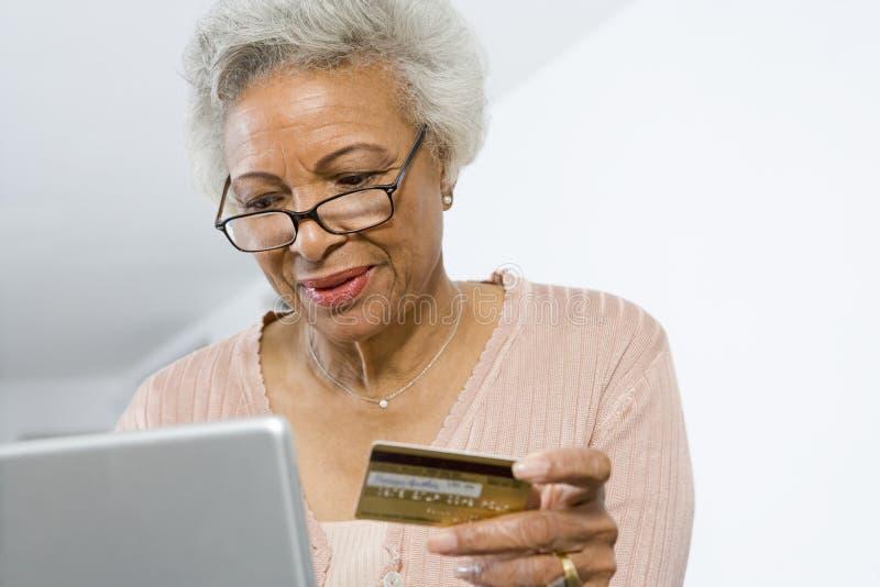 Hög kvinna som direktanslutet shoppar arkivfoton