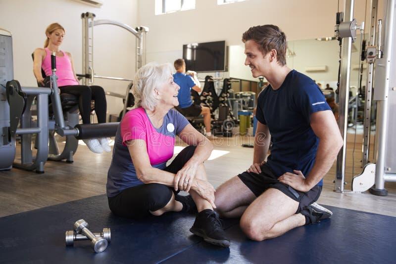 Hög kvinna som diskuterar övningsprogram med den manliga personliga instruktören In Gym arkivbilder