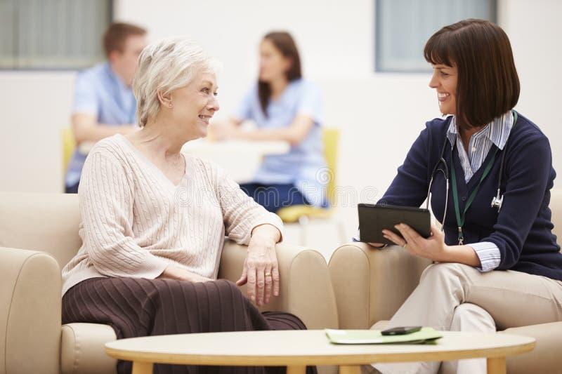 Hög kvinna som diskuterar provresultat med doktorn arkivfoton