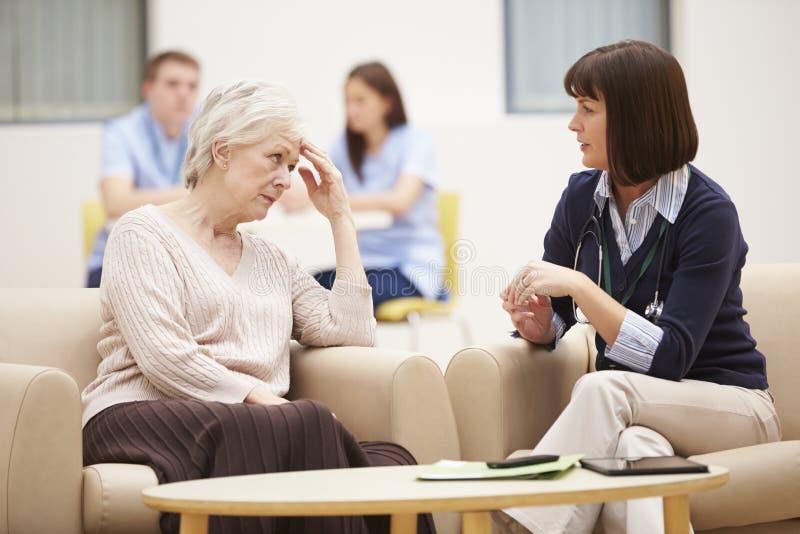 Hög kvinna som diskuterar provresultat med doktorn royaltyfri foto