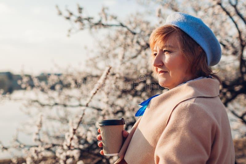 Hög kvinna som dricker kaffe och kopplar av i vårträdgård Fostra dagbegreppet f?r ` s royaltyfria foton